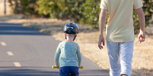一个骑着车的小孩子和一个穿短袖的大人